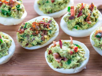 Bacon guacamole deviled eggs sitting on a wooden cutting board.