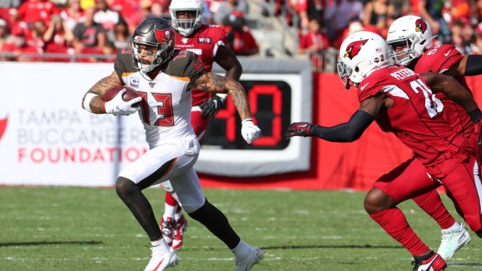 NFL Tampa Bay Buccaneers wide receiver Mike Evans running after the catch with the football against the Arizona Cardinals defense.