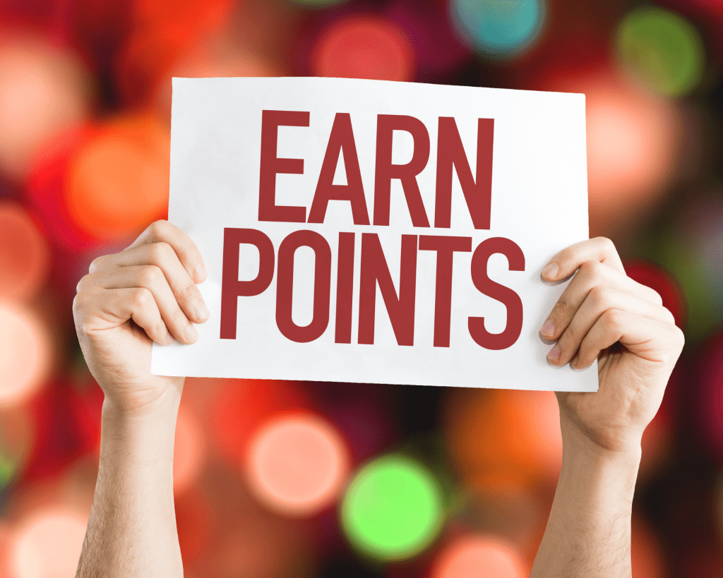 A person holding up a sign that says EARN POINTS