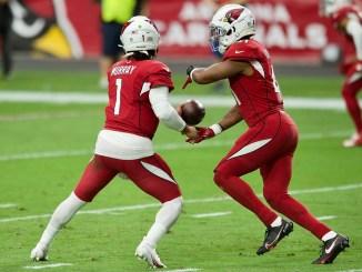 NFL Arizona Cardinals quarterback Kyler Murray giving a handoff on the football field to running back Kenyan Drake