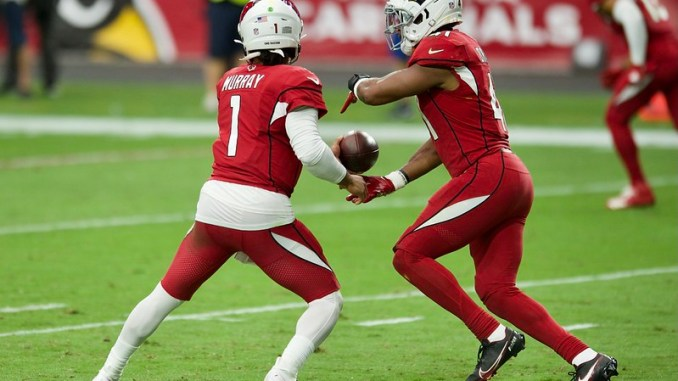 NFL Arizona Cardinals quarterback Kyler Murray giving a handoff on the football field to running back Kenyan Drake
