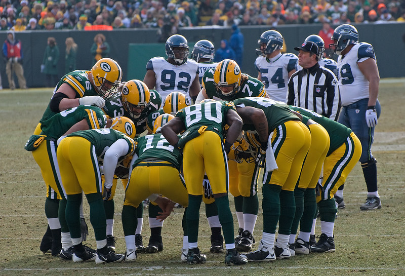 The Green Bay Packers offense huddled up on the football field during an NFL game