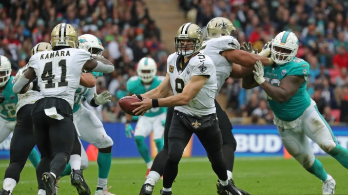NFL New Orleans Saints running back Alvin Kamara taking a handoff from New Orleans Saints quarterback Drew Brees in a football game against the Miami Dolphins.
