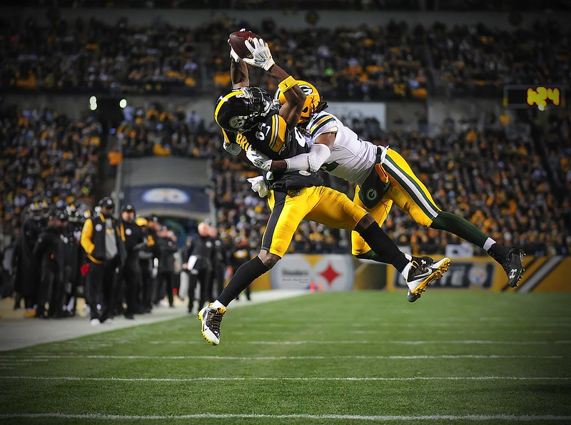 NFL wide receiver Antonio Brown going up for a contested catch against a Green Bay Packers defender