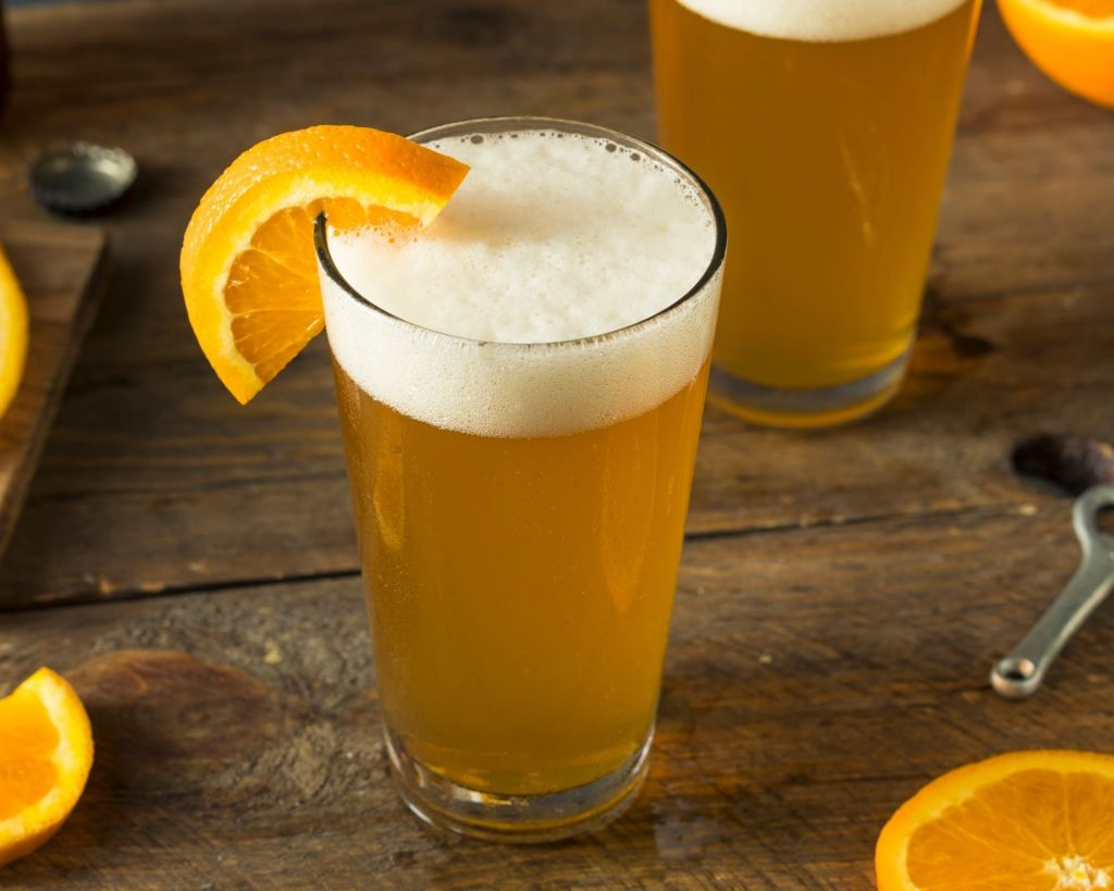 A couple of pints of Beermosa's garnished with fresh orange slices sitting on a wooden table with a silver bottle opener and bottle caps popped off.