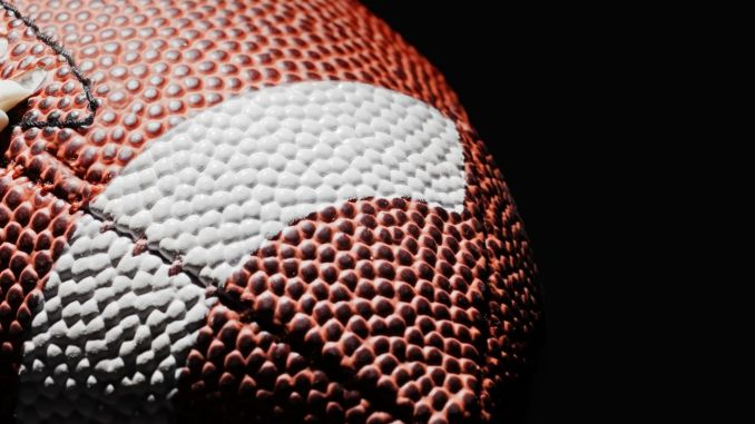 A brown football on a black background