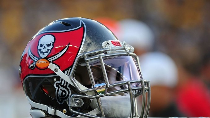 A NFL Tampa Bay Buccaneers helmet sitting on the sideline