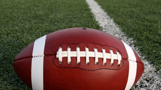 A football on the 50 yard line on a football field.