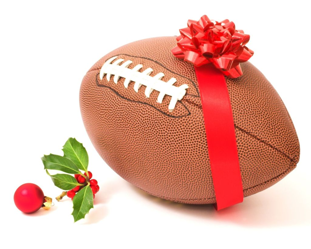 A holiday American football wrapped in a red bow. Red and green holly berries and a red christmas ornament of to the side.