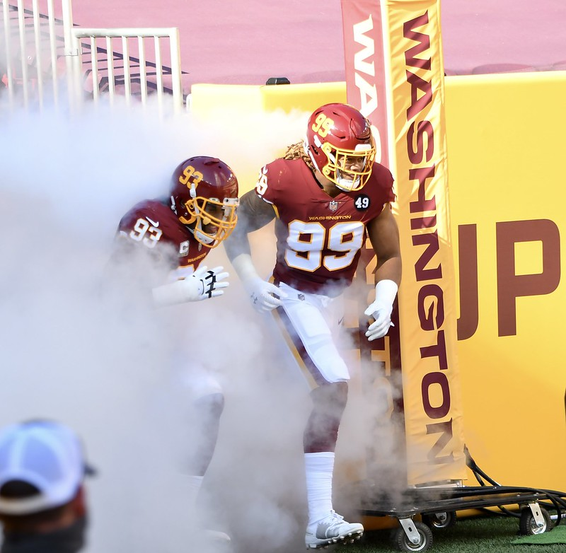Washington Football Team defensive end Chase Young and Jon Allen running out of the tunnel with smoke behind them.