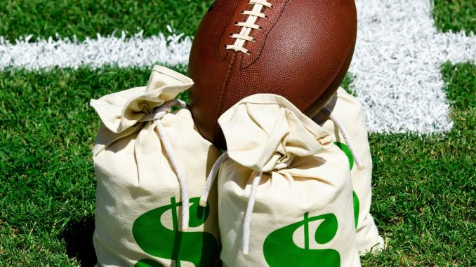 A football sitting on top of bags of money sitting on a football field.