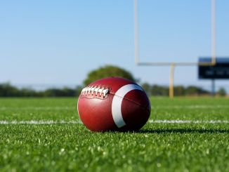 A football sitting in the middle of a football field with goal posts in the background.
