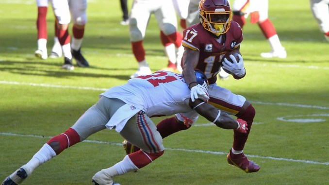 NFL Washington Football Team wide receiver Terry McLaurin dodging a tackle against a New York Giants defender