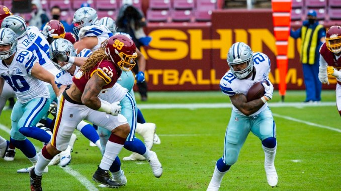 Dallas Cowboys running back Ezekial Elliott trying to avoid a tackle from Washington Football Team defensive end Chase Young in a football game.