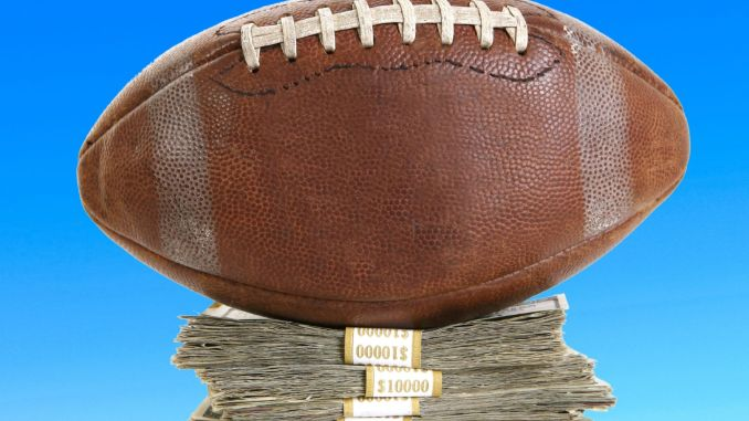 Football sitting on a pile of money