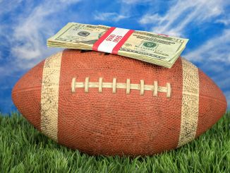 $500 laying on top of a football sitting in the grass with the blue sky in the background.