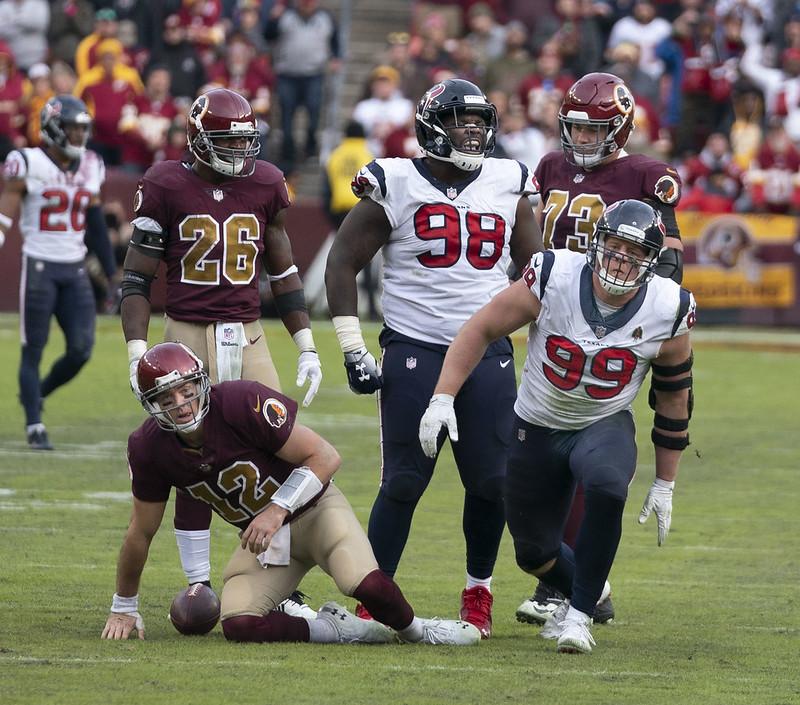 NFL Houston Texans defense sacking the Washington Football Teams quarterback in a football game.