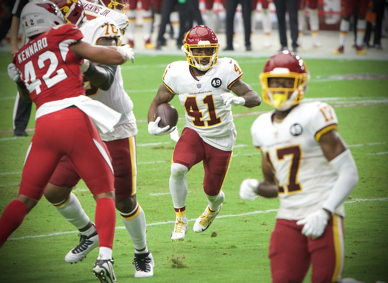 Washington Football Team running back J.D. McKissic running through a whole against the Arizona Cardinals defense.