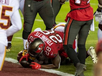 NFL Tampa Bay Buccaneers running back Leonard Fournette scoring a touchdown from the one yard line against the Washington Football Team in the Wild Card Round Playoffs.