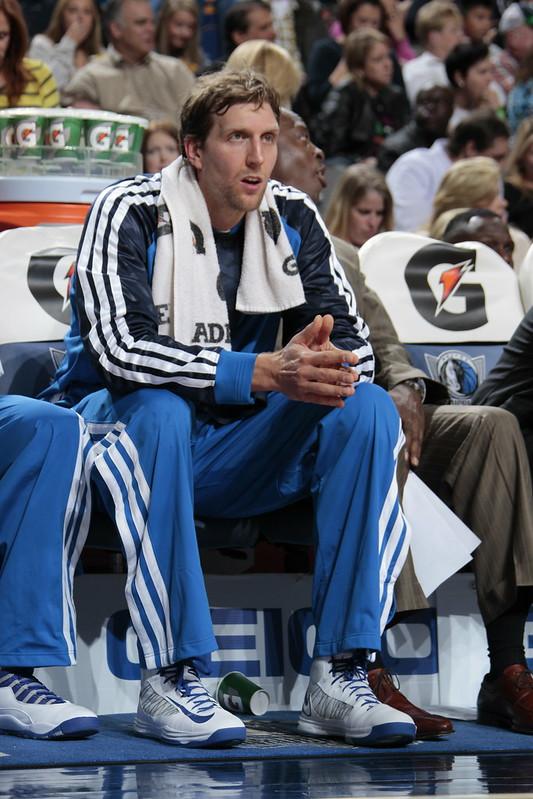 NBA legendary Dallas Mavericks power forward Dirk Nowitzki sitting on the bench in a basketball game.