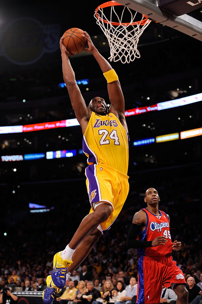 NBA legendary Los Angeles Lakers shooting guard Kobe Bryant flying through the air to dunk the basketball on a Los Angeles Clippers defender.