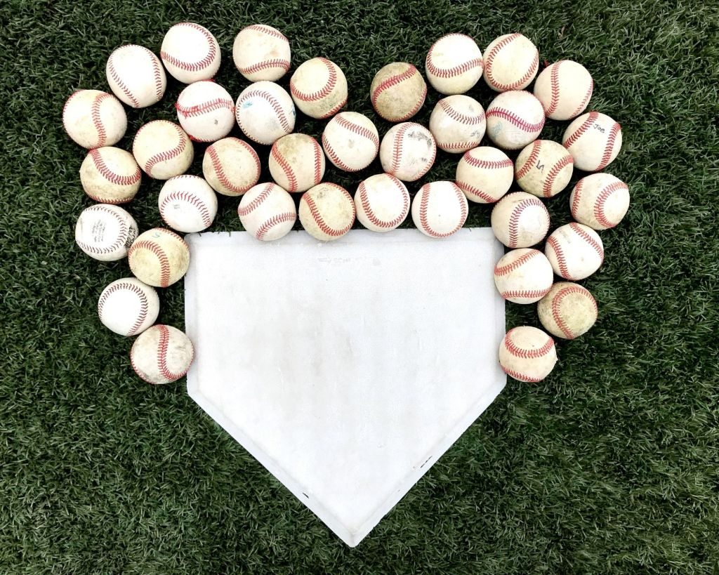 Baseballs and home plate in the shape of a heart.