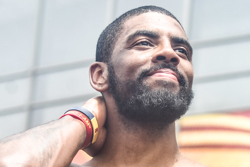 NBA basketball player Kyrie Irving posing with his hand behind his head.