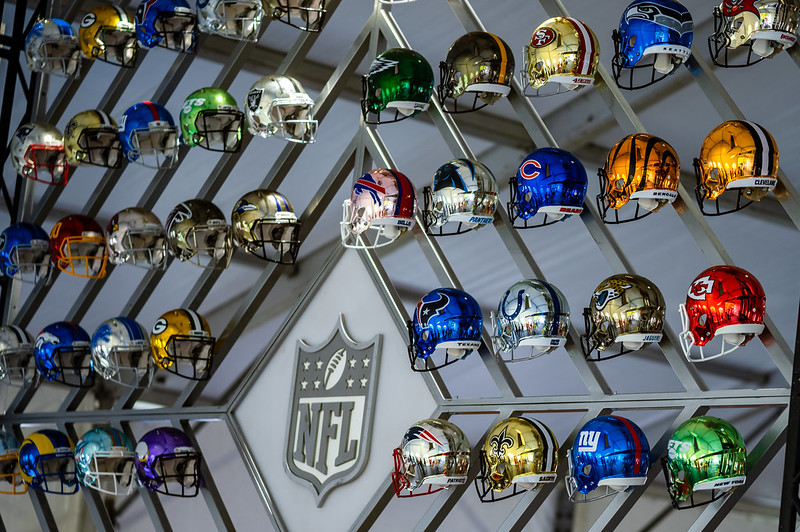 A collection of NFL helmets on a wall at the 2021 NFL Draft Experience in Cleveland, Ohio.