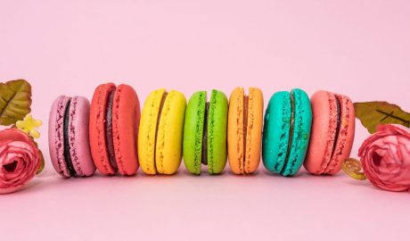 Multicolored French Macarons On A Pink Background With Roses