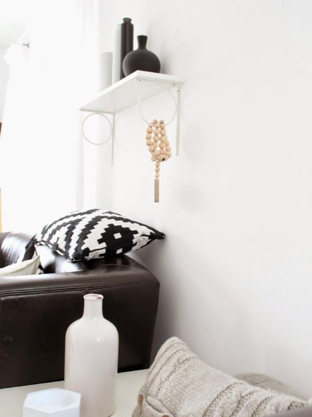 Schräger Blick aufs braune Sofa mit Regal und Deko in Weiß