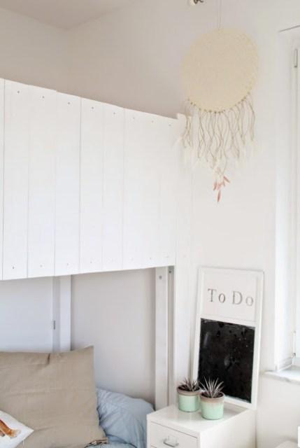 Blick ins Kinderzimmer mit Traumfänger, der an einem weißen Hochbett hängt unter dem Hochbett ein Sofa mit Kommode und Kakteendeko