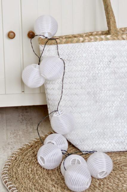 Lichterkette ragt aus weißer Korbtasche heraus