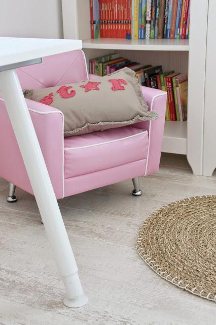 Ansicht Bücherregal mit pinkem Sessel davor