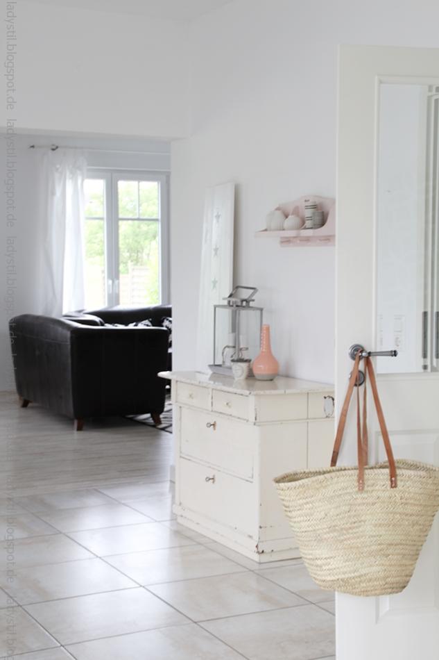 Esszimmertür mit Korbtasche und Blick auf die beige Kommode mit rosa Accessoires und ins Wohnzimmer
