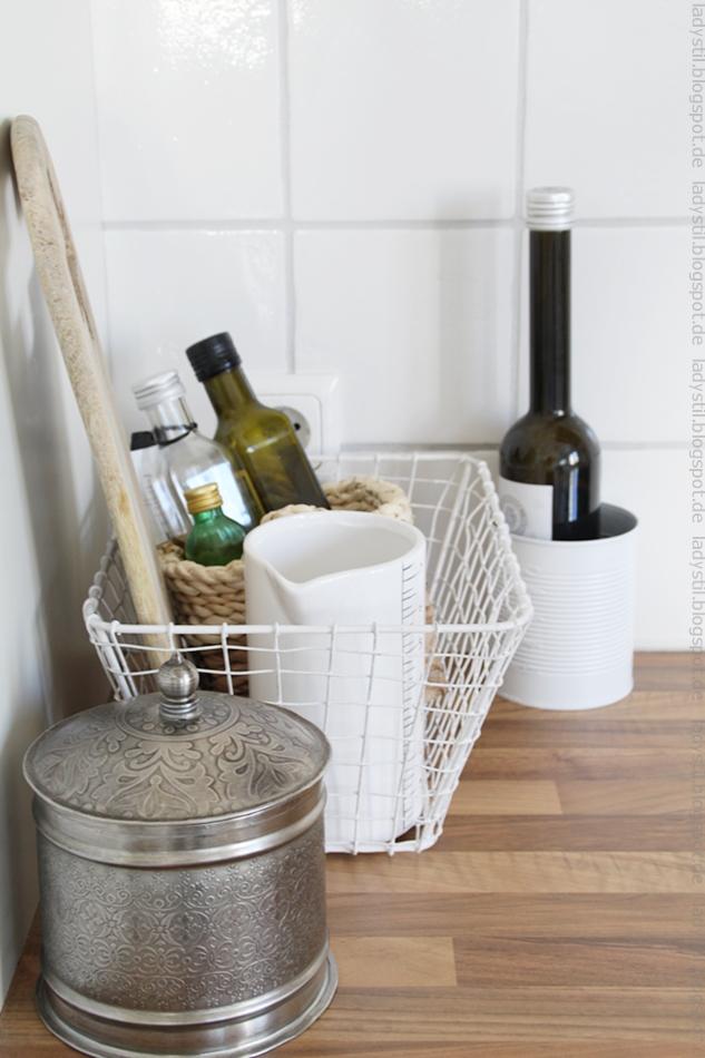weißer Drahtkorb, indem Essig und Ölflaschen untergebracht sind, weißer Messbecher aus Keramik von House Doctor, davor eine marikkanische silberne Dose