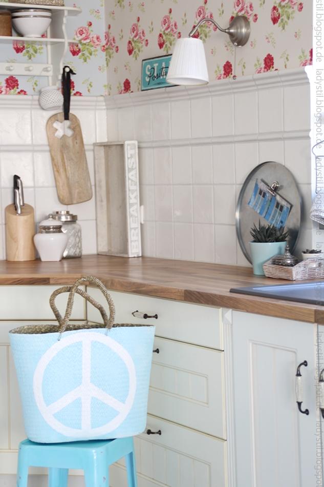 Blick auf die Küchenzeile mit Deko in Holz, Türkis und weiß davor steht der hellblaue Korb mit Peacezeichen