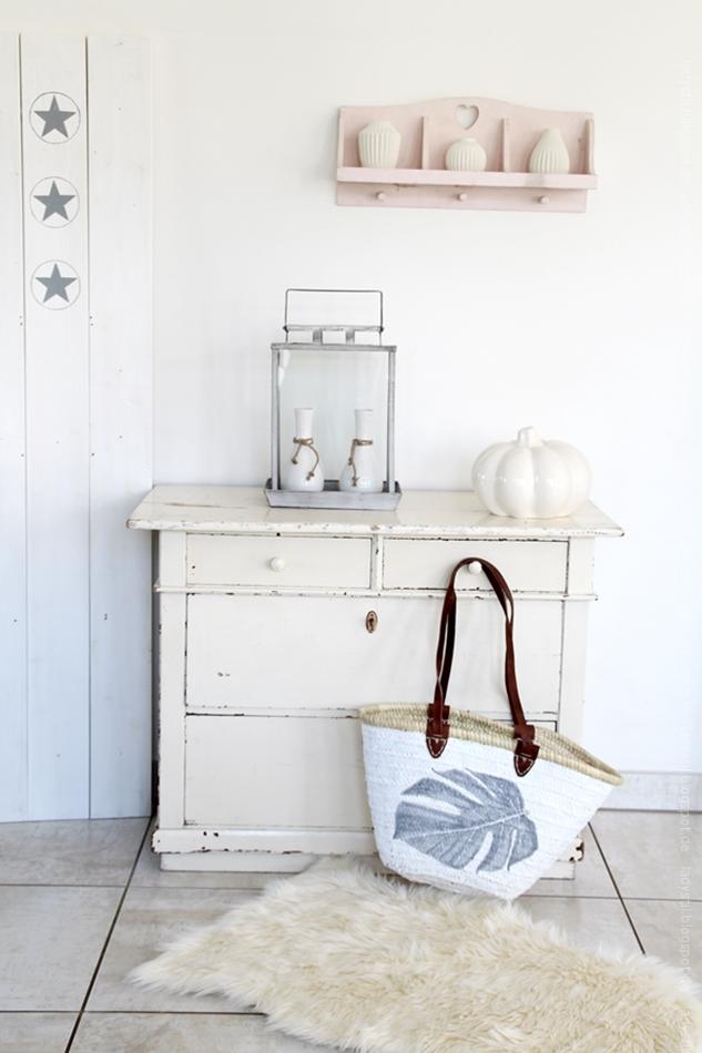 eine mit einem Monsterablatt bemalte Korbtasche vor einer Shabby-Kommode mit weißer Kürbisdekoration
