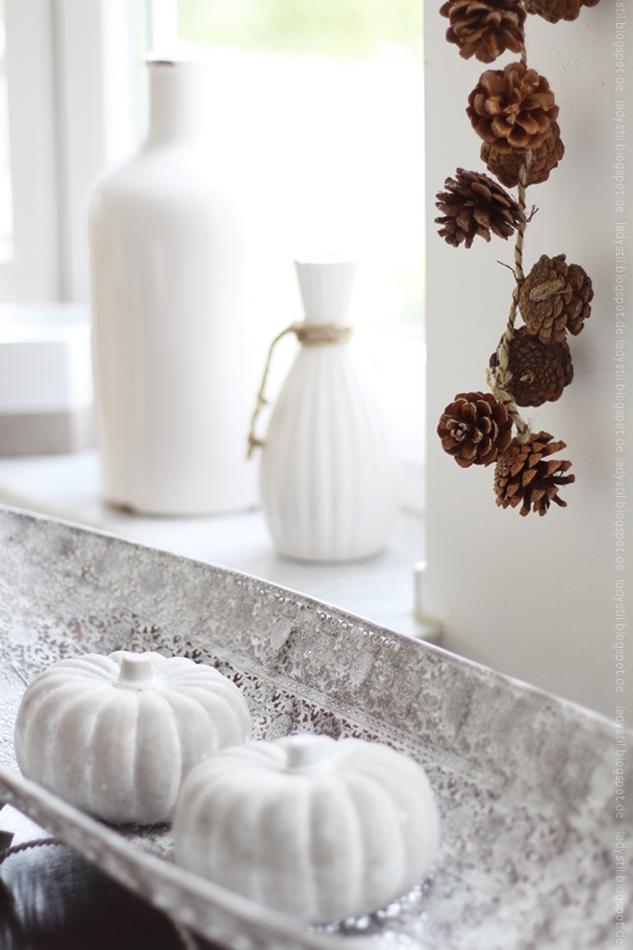 Herbstimpressionen Deko einer Tannenzapfengirlande mit weißen Accessoires und grauen Kürbissen