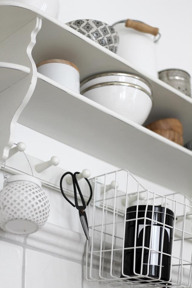 """Blick auf das weiße Küchenregal mit Accessoires von House of Ideas und Dose """"T"""" von Nicolas Vahe"""