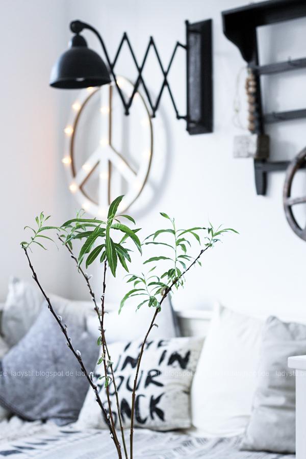 DIY Peacezeichen Leuchtobjekt im Hintergrund, Vordergrund Weidenkätzchen in Glasvase auf Hocker