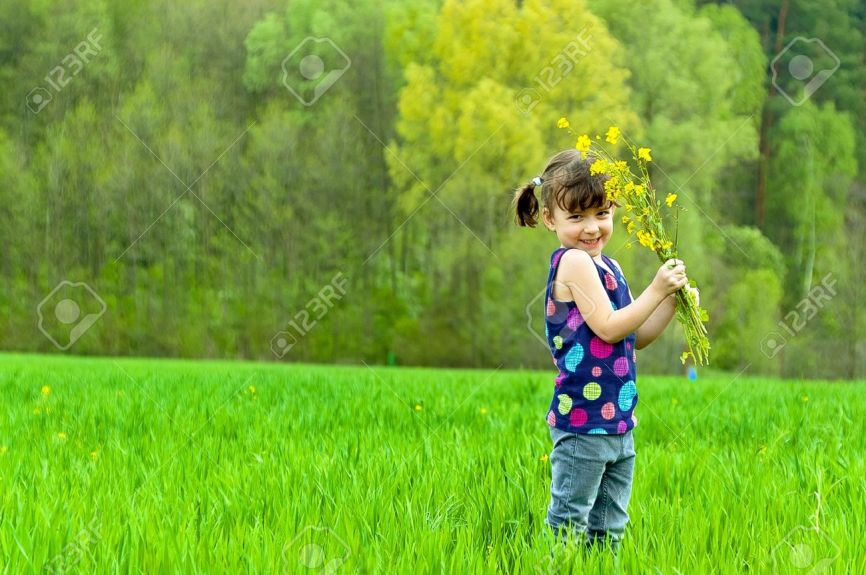 9485322-Little-girl-with-flowers-on-green-field-Stock-Photo-child