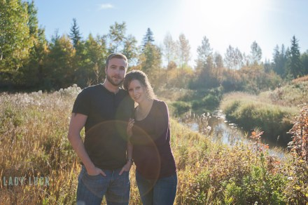 outdoor-maternity-portraits-blackmud-creek-edmonton-couple-standing-by-the-river-nicole-leaning-on-her-husband