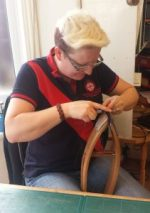 Image of Clair learning to stitch using a saddler's clam in 2015