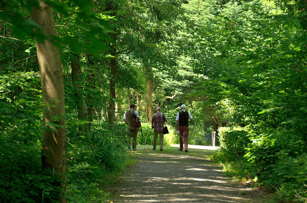 Customers walking down a path in the grounds of Lady's Wood Shooting School