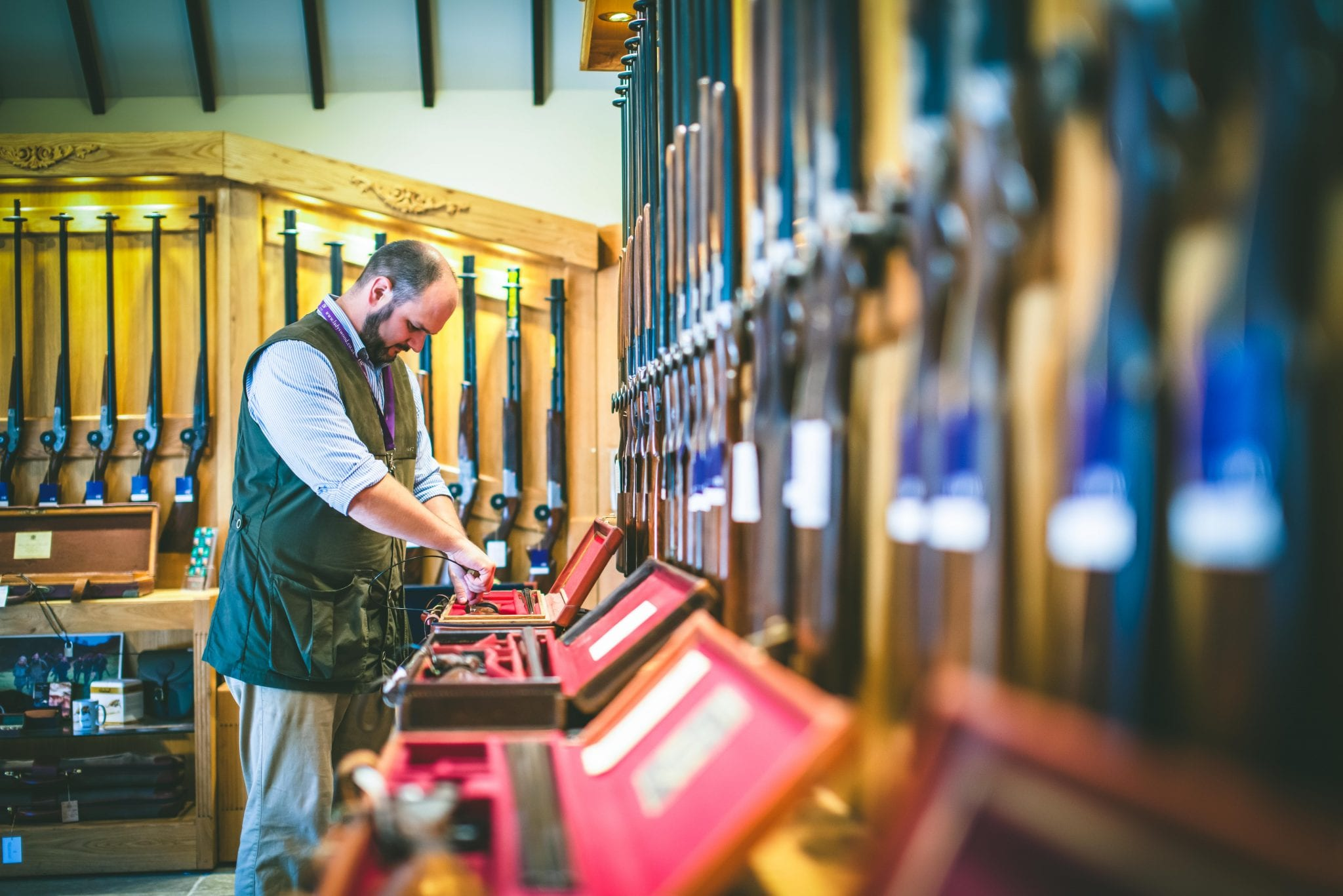 Shooting school manager Chris Hanks looks at a shotgun in the Sportarm at Lady's Wood gun room