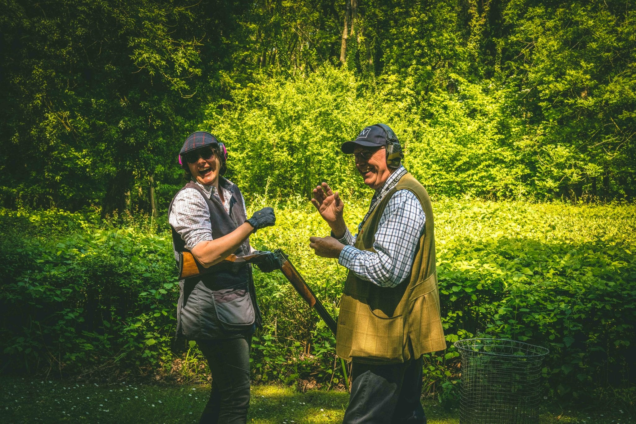 A shooting instructor and customer enjoy a clay shooting lesson