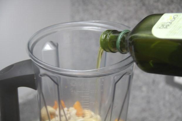 Agregar el aceite de oliva, cashews, ajíes, agua y sal.