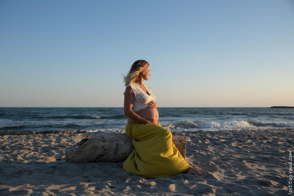 femme enceinte assise sur un rondin de bois