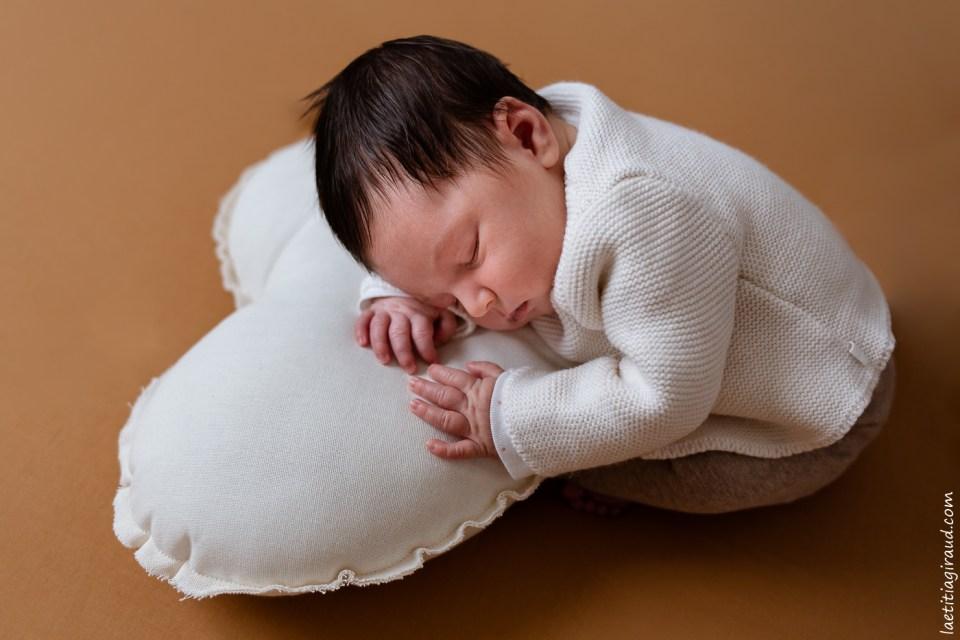 photo nouveau né posé sur un coussin en forme de coeur