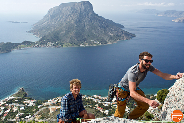2 climbers arriving at the top of a route. On the background, the Telendos Island
